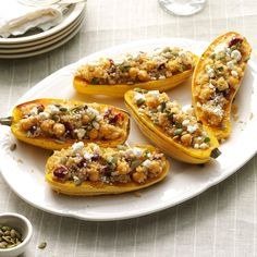 """Quinoa-Stuffed Squash Boats Recipe -My colorful """"boats"""" with quinoa, chickpeas and pumpkin seeds use delicata squash, a winter squash that's cream-colored with green stripes. In a pinch, acorn squash will do. —Lauren Knoelke, Milwaukee, Wisconsin"""