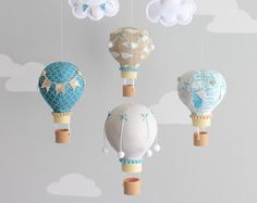 Blush pink and grey baby mobile in a hot air balloon theme. The photos show 5 hot air balloons floating under two puffy clouds. Each balloon is hand made from various coordinating fabrics and adorned with different bunting flags, bakers twine, buttons, pompoms and little baskets, printed using 3D technology, give it a real look of wicker. They all hang from a wooden mobile finished off with two strings of tiny bunting flags. You may personalize one of the clouds with baby's name and or…