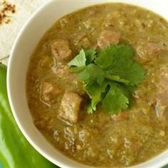 Pork stew meat is simmered in a tomatillo sauce with garlic, serrano, and chile de arbol peppers for a spicy, saucy meat stew that's great for piling into warm tortillas.