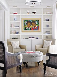 British colonial cane chairs by Drexel Heritage, a tufted ottoman from Thomasville and a pair of comfy lounge chairs from Bernhardt create a cozy conversation spot off the living room. The painting is by Jean Bernard Etienne.