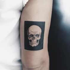 Realistic white skull tattoo inked in the solid black rectangle on the right upper arm above the elbow