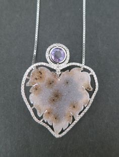 An 18k white gold cherub with a speckled druzy body and 0.60 total carat weight champagne diamonds and a 0.77 carat rose cut purple sapphire. This was designed and made by llyn strong.