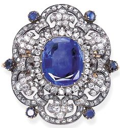 1880s antique sapphire and diamond brooch set with a central cushion-shaped sapphire weighing 30.55 carats, with an old mine-cut diamond border, to the old mine-cut diamond scrolled frame with fleur-de-lys detail and collet-set sapphire intersections. #SapphireBrooch #BelleEpocheBrooch