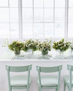 Centerpieces of viburnum, snowberry, bells of Ireland, asclepias pods, and carnations in salt-glass vessels exude a feeling of warm modernity.
