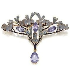 c1900  Pendant/Brooch of sapphire, enamel and moulded glass by René Lalique The fan-shaped spray decorated w moulded glass buds and pale blue enamelled leaves on a dark blue enamelled branches, further decorated w 3 marquise-shaped sapphires, anchored by a pear-shaped sapphire drop, mounted in gold, signed Lalique