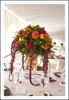 Elevated centerpiece with Circus roses, freesia, hanging amaranthus, orchids by Love In Bloom Florist, Key West at Ocean Key Resort. Photo by Transier Photography