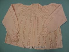 From the 1950s pattern published by Patons & Baldwins, it has a smocked effect yoke and cuffs, and lacey panels. It might have been knitted from wool that had been knitted previously.