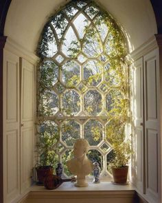 Gothic Revival window with vining plants inside.