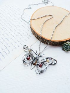 Unique silver butterfly necklace with Garnet and smoky quartz by Ursula Jewelry.