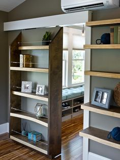 """Upstairs in the master suite, this clever sliding bookshelf provides storage and a secret entrance into the master bedroom. Custom, curvy bookshelves mimic the lake's natural beauty. """"Instead of painting the edge, it's sealed to bring out the varying layers of the plywood,"""" explains Dylan. Wires line the sliding bookshelf to keep books and accessories in tacked."""