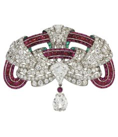 AN ART DECO RUBY, EMERALD AND DIAMOND BROOCH, BY JANESICH. Composed of a pavé-set buff-top ruby frame interwoven with a pierced stylised single, old and baguette-cut diamond-set ribbon, to the central kite-shaped diamond 'knot', suspending a single old-cut pear shaped diamond drop, 1920s, 6.4 cm, with French assay marks for platinum and gold. #Janesich #ArtDeco #brooch