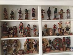 Kachina doll and basketry display on shelving in den.