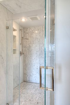 Mosaic tile on one wall and across shower floor, shower nooks, Calacatta Gold sinuous polished water jet mosaic from the Musee collection and Calacatta Gold. great shower door handle