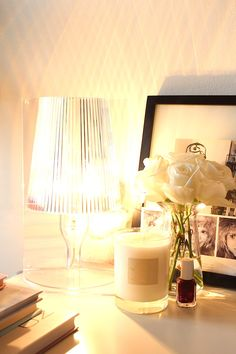 A PLACE OF MY OWN  |  SHADES OF STYLE  :: kartell lamp shines brightly on my desk along with coffee table books, voluspa candle and some fresh white roses.