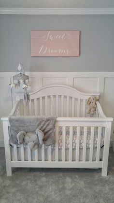 "Sweet and calm gray nursery. White crib, white DIY board and batten, elephant play mat, ""Sweet Dreams"" canvas. Gray paint color is Valspar's ""Bay Waves"". #boardandbatten"