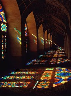 The sun streaming through beautiful stained glass windows beaming multicolored rays onto the floor.