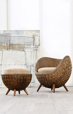 Rattan chair & ottoman with natural cushions in front of an abstract art canvas. I could curl up in this chair all day!