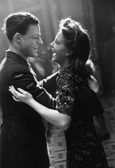 An airman shares a joke with his girlfriend as they dance at a dance hall. April 22, 1944.