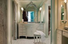 a Venitian mirror on a wall of mirrors makes this bathroom really interesting