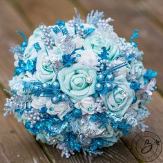 Frozen Glitter Blue winter wedding bouquet with silver, aqua and turquoise glitter accents  Get the perfect bouquet for your winter wedding themed wedding! This sparkly work of art is a show stopper with various aqua, turquoise and silver accents, and white soft-touch roses and sparkly gems. Few white snowflakes are tucked between the roses for the perfect winter-y accent that will fit any winter wedding. Let us make your dream bouquet and make the stress go away! Bottom is lined with…
