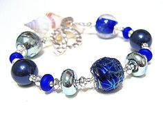 Stunning bracelet featuring co-ordinating blue lampwork beads handmade by UK artisan complimented by Swarovski Night Blue crystal pearls, etched lampwork spacers and sterling silver beads finished with a hammered Karen Hill Tribe Silver clasp.