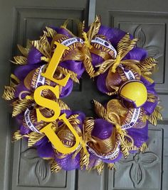 "This is a hand crafted Louisiana State University 24"" deco mesh wreath. It is made of purple and yellow gold mesh with purple and gold ""tiger"" ribbons and accented with hand painted LSU letters and a"