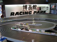 Huge slot car track at the toy store.     Slot cars are powered small vehicles that are assisted by a slot or groove set in the tracks on which they run. At the bottom of the car is a blade or pin that keeps the car in the slot. To make the car run, the metal strips placed next to the slot d