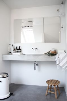 concrete vanity + white walls + exposed bulb + minimal bathroom