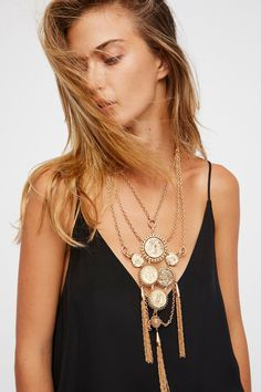 Clustered Medallion Pendant     Statement metal necklace featuring a large medallion pendant.   * Metal tassel accents. * Multiple chains * Lobster clasp closure * Adjustable fit