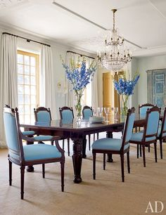 A dining room is enlivened by an ornate chandelier and South African chairs upholstered in a Duralee fabric | archdigest.com