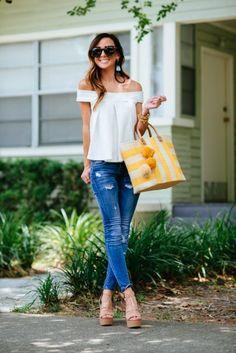 Chica usando una blusa sin hombros, pantalón de mezclilla y sosteniendo un bolso en color amarillo