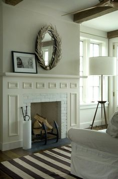 Lovely family room design with white & brown striped rug, rustic wood beams, white fireplace with herringbone firebox, wood tripod floor lamp, white, linen, slip-covered sofa and oval mirror.