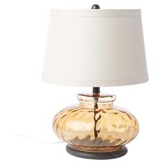 Cast a warm glow in your living room or reading nook with this eye-catching table lamp, showcasing a brown-hued glass base.