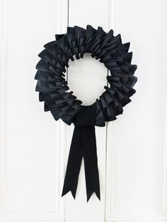 Black Crepe Paper Wreath:  Cut 4 inch strips and fold them in half.  Pin three strips side by side so they overlap to form one row from outside edge to inner edge.  Directly beneath that row, pin another row, overlapping the pinned edges so they don't show. Continue around the wreath, finishing with a streamer looped over the last bit of space. Trim ends into a V and fluff the loops.