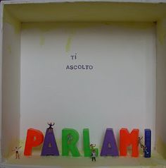 """This display case is consecrated to the opening, to the dialogue. The inscription """"ti ascolto""""/""""I am listening to you"""" resides in an empty and neutral space in the background: it means that there is no prejudice, no preconception, only the willingness to listen to whatever can be told, giving free hand, filling this open space with words, with a tale, with any form of communication."""