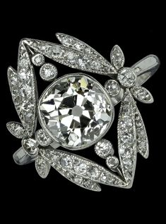 A Belle Epoque platinum and diamond ring, the central cushion-shaped old brilliant-cut diamond millegrain collet set within a garland surround set with graduated old single and rose-cut diamonds, mounted in platinum, with engraved scroll detail to the sides of the mount.