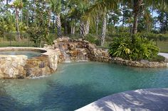 Free-shape fenced in pool with stone spa and stone waterfall feature and a nice plantar area