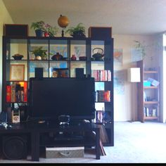 This is my living room, viewed from the couch. We used the Expedit bookcase from Ikea as a room divider, and put maps on the wall behind it. We use the space behind it as a small office area, with a desk and the record player. My father built the smaller bookshelf in the corner.