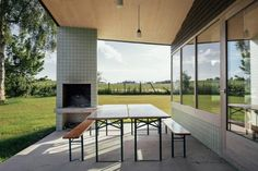 Dark clay panels and light green tiles cover the cross-laminated timber structure of this holiday home