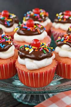This Hot Fudge Sundae Cupcakes recipe starts with strawberry cupcakes topped with vanilla buttercream, chocolate ganache, sprinkles, and a cherry on top!