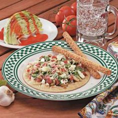 Greek Pita Pizzas Recipe -Pita bread is the crust for these single-serving pizzas that get Mediterranean flair from olives, spinach and feta cheese. Breadsticks and a wedge of iceberg lettuce drizzled with salad dressing (pictured above right) make fine pizza partners. Or serve an appetizer of fresh vegetables with dip, then cap off the meal with lemon Italian ice.