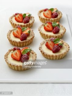 Stock Photo : White chocolate and mascarpone tartlets, decorated with strawberries, raspberries and mint leaves, close-up