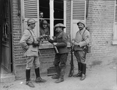 French (25th Dragoon Regiment ) and British troops sharing a drink outside an estaminet in the Amiens sector, 26 April 1918.