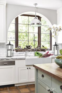 The kitchen features plenty of sunlight and romantic archways that mark the house's Spanish-style architecture. Marble countertops are juxtaposed with terra-cotta tile flooring and add luxury to the room, which White transformed by changing dark cherry cabinetry to bright white.