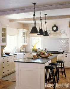 The kitchen ceiling is faced in 300-year-old floor beams, rescued from an old barn and whitewashed. This Vermont kitchen is designed by Susan Tully.