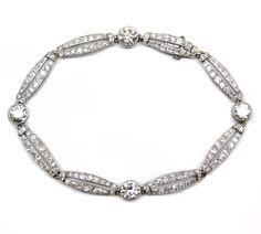 Early 20th century diamond bracelet, French c.1910  , designed as a row of elongated oval links, each formed by two lines of diamonds, spaced by four round brilliant cut diamonds in rubover settings, mounted in platinum