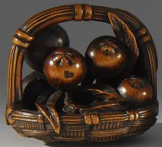 Lot 18: WOOD NETSUKE By Mitsuhiro. In the form of fruit lying in a basket with a fly sitting on one of the pieces of fruit. Signed. - Eldred's | Invaluable