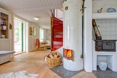 Don't you just love the red staircase, the fireplace and the stove? This Swedish home is full of country charm.