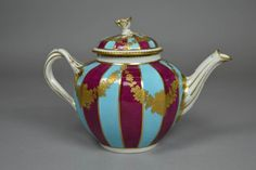 Teapot and cover; porcelain; fluted sides alternately crimson and turquoise with gilt festoons; twisted handle; flower knop on cover; marked.