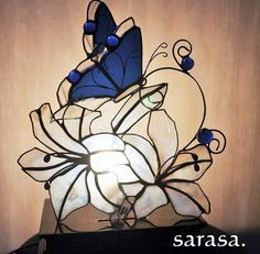 ステンドグラスで制作した平面ファンランプ♪清楚で豪華な白い百合の花に青い蝶が香りに引き寄せられて・・・そんな光景を作品で表現してみました(*´▽`...|ハンドメイド、手作り、手仕事品の通販・販売・購入ならCreema。 Stained Glass Lamp Shades, Creema, Diy Projects, Illustration, Flowers, Artist, Handmade, Crafts, Character